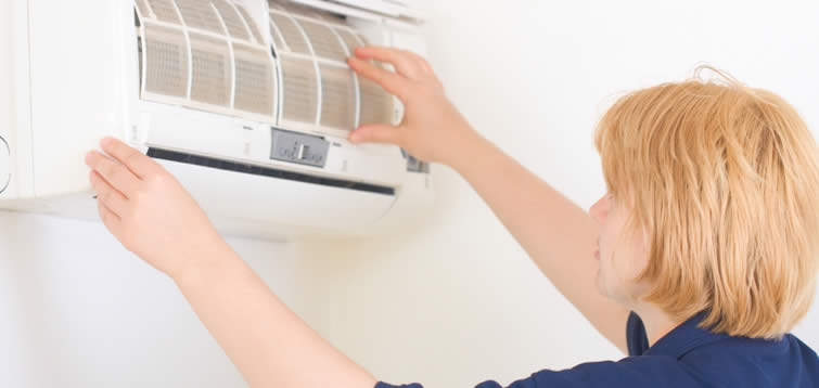 Woman cleaning an AC unit